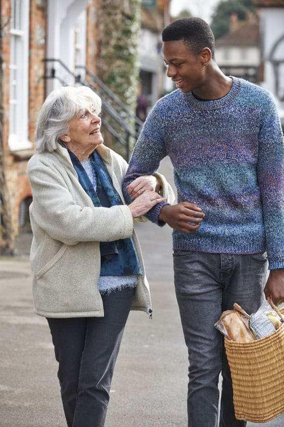 Teenage Boy Helping Senior Woman with Shopping